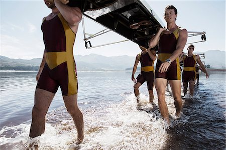 sport rowing teamwork - Rowing team carrying scull out of lake Stock Photo - Premium Royalty-Free, Code: 6113-07588812