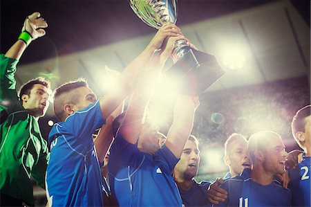 football team - Soccer team celebrating with trophy on field Stock Photo - Premium Royalty-Free, Code: 6113-07588838