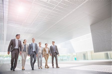 Business people walking in modern courtyard Stock Photo - Premium Royalty-Free, Code: 6113-07588900