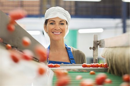Portrait of smiling worker examining tomatoes at conveyor belt in food processing plant Stock Photo - Premium Royalty-Free, Code: 6113-07589256