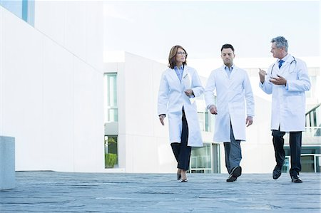 Doctors walking and talking on roof Stock Photo - Premium Royalty-Free, Code: 6113-07589261