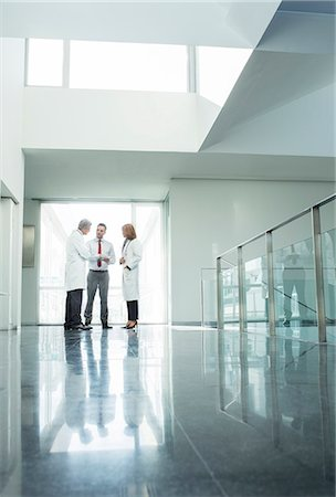 Doctors and administrators talking in hospital corridor Stock Photo - Premium Royalty-Free, Code: 6113-07589273
