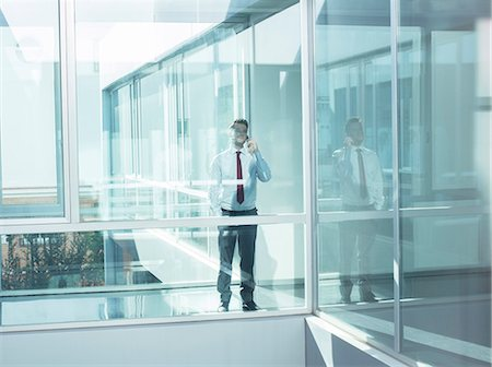 Businessman talking on cell phone in modern office Stock Photo - Premium Royalty-Free, Code: 6113-07589275