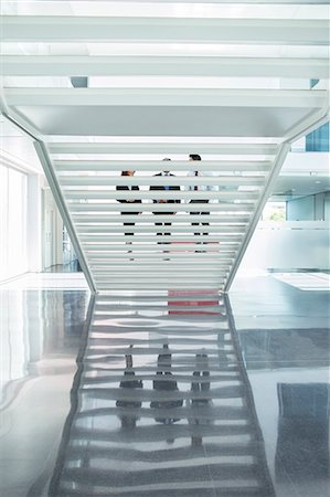Business people ascending modern staircase in office Stock Photo - Premium Royalty-Free, Code: 6113-07589282