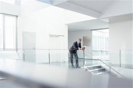 Businessman using digital tablet in corridor Stock Photo - Premium Royalty-Free, Code: 6113-07589286