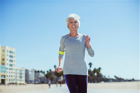 senior women - Senior woman power walking on beach Stock Photo - Premium Royalty-Free, Code: 6113-07589348