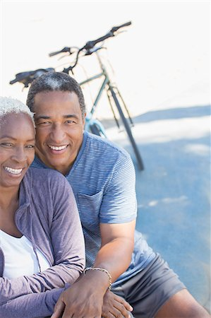 Portrait of smiling senior couple near bicycle Stock Photo - Premium Royalty-Free, Code: 6113-07589354