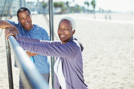 Portrait of senior couple leaning on bar at beach playground Stock Photo - Premium Royalty-Free, Code: 6113-07589371