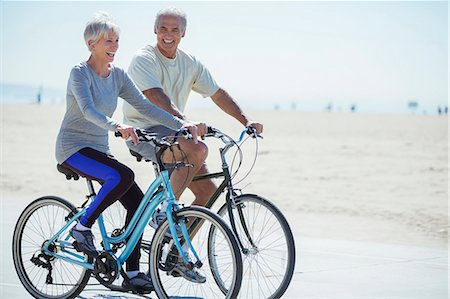 senior women - Senior couple riding bicycles on beach boardwalk Stock Photo - Premium Royalty-Free, Code: 6113-07589377