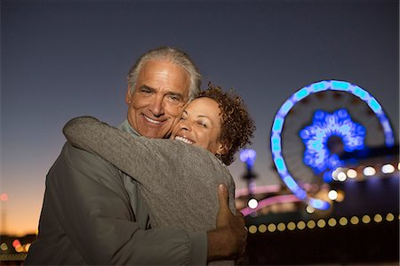 Portrait of couple hugging outside amusement park at night Stock Photo - Premium Royalty-Free, Code: 6113-07589378