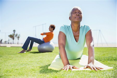 Women practicing yoga in sunny park Stock Photo - Premium Royalty-Free, Code: 6113-07589390