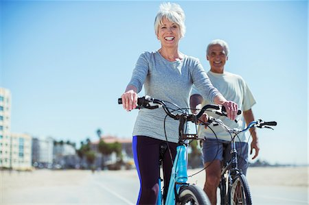 Portrait of senior couple with bicycles on beach boardwalk Stock Photo - Premium Royalty-Free, Code: 6113-07589391