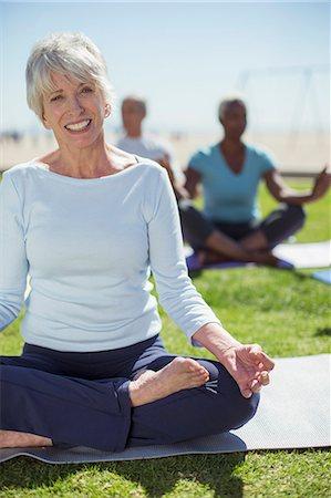 Portrait of smiling senior woman practicing yoga in park Stock Photo - Premium Royalty-Free, Code: 6113-07589397
