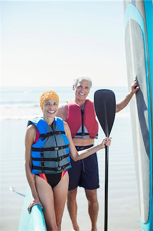 Portrait of senior couple with paddleboards on beach Stock Photo - Premium Royalty-Free, Code: 6113-07589398