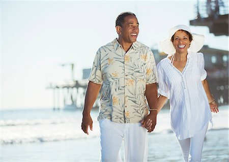 Couple holding hands and walking on beach Stock Photo - Premium Royalty-Free, Code: 6113-07589328