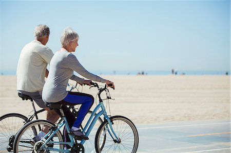 Senior couple riding bicycles on beach Stock Photo - Premium Royalty-Free, Code: 6113-07589331