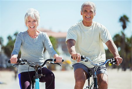 Portrait of senior couple riding bicycles on beach Stock Photo - Premium Royalty-Free, Code: 6113-07589334