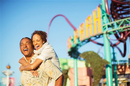 Enthusiastic couple hugging at amusement park Stock Photo - Premium Royalty-Free, Code: 6113-07589441