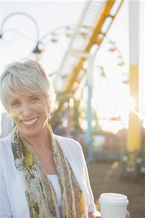 Portrait of smiling senior woman drinking coffee at amusement park Stock Photo - Premium Royalty-Free, Code: 6113-07589459