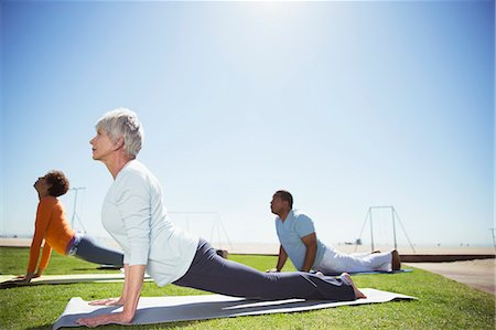 Seniors practicing yoga in sunny beach park Stock Photo - Premium Royalty-Free, Code: 6113-07589482