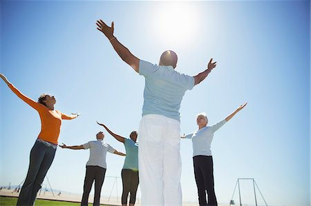 Seniors practicing yoga under sunny blue sky Stock Photo - Premium Royalty-Free, Code: 6113-07589484