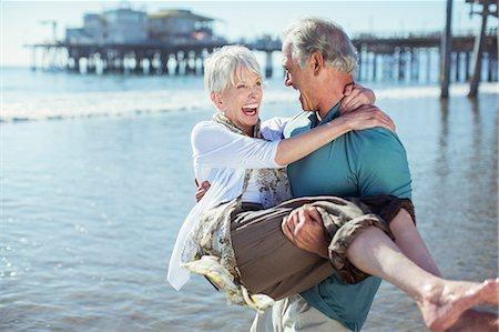 Senior man carrying wife on sunny beach Stock Photo - Premium Royalty-Free, Code: 6113-07589402