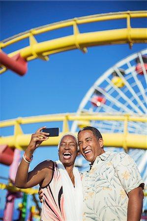 Senior couple taking selfie at amusement park Stock Photo - Premium Royalty-Free, Code: 6113-07589414
