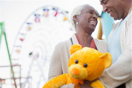 enjoying - Senior couple with teddy bear hugging at amusement park Stock Photo - Premium Royalty-Free, Code: 6113-07589420