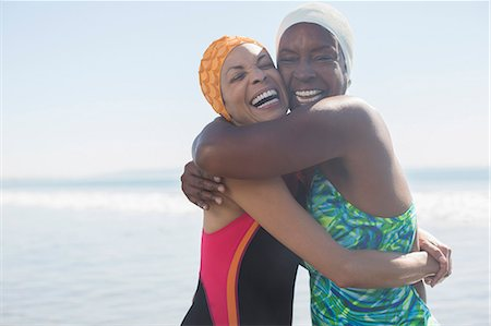 Enthusiastic women hugging in bathing suits and caps Stock Photo - Premium Royalty-Free, Code: 6113-07589433