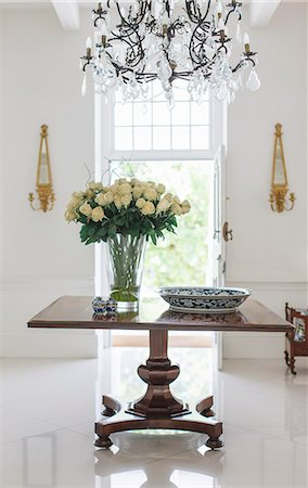 Chandelier over bouquet on table in luxury foyer Stockbilder - Premium RF Lizenzfrei, Bildnummer: 6113-07589570
