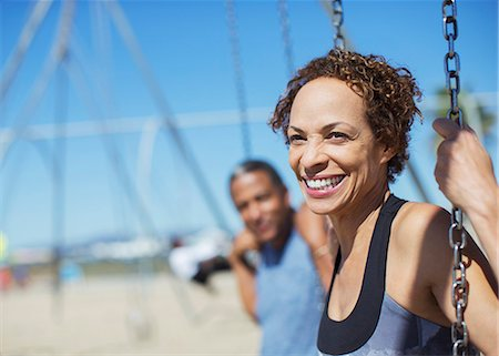 Happy couple on swings at playground Stock Photo - Premium Royalty-Free, Code: 6113-07589503