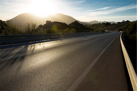 Sun shining over mountains and open road Stock Photo - Premium Royalty-Free, Code: 6113-07589510