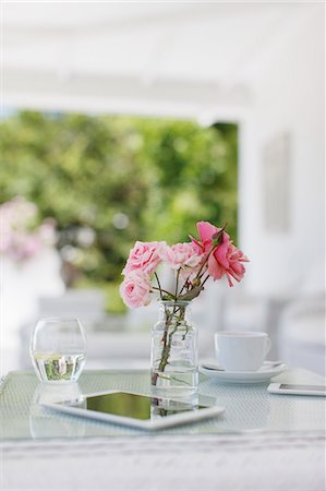 still life - Pink roses on patio table next to coffee cup and digital tablet Stock Photo - Premium Royalty-Free, Code: 6113-07589613
