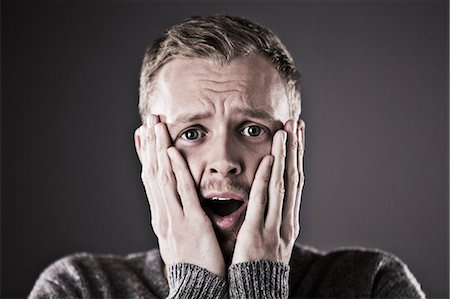 people in panic - Portrait of surprised man with head in hands Stock Photo - Premium Royalty-Free, Code: 6113-07648678
