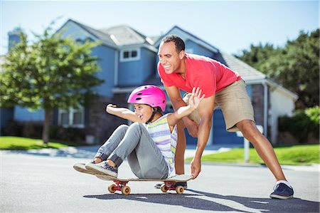 playing - Father pushing daughter on skateboard Stock Photo - Premium Royalty-Free, Code: 6113-07648771