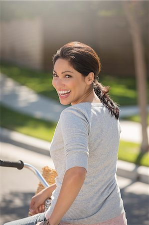 Portrait of enthusiastic woman on bicycle Fotografie stock - Premium Royalty-Free, Codice: 6113-07648780