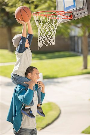 Father and son playing basketball in driveway Stock Photo - Premium Royalty-Free, Code: 6113-07648784