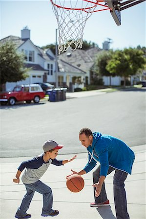 playing - Father and son playing basketball in driveway Stock Photo - Premium Royalty-Free, Code: 6113-07648786