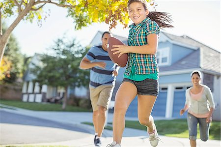 Family playing football in sunny street Stock Photo - Premium Royalty-Free, Code: 6113-07648790