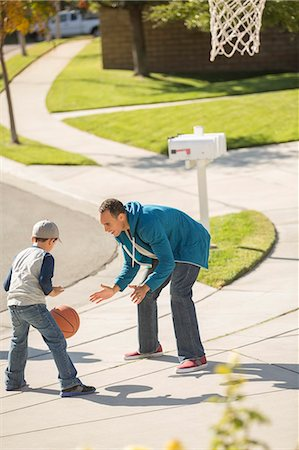 Father and son playing basketball in sunny driveway Stock Photo - Premium Royalty-Free, Code: 6113-07648842