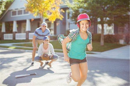 Family playing baseball in street Stock Photo - Premium Royalty-Free, Code: 6113-07648851