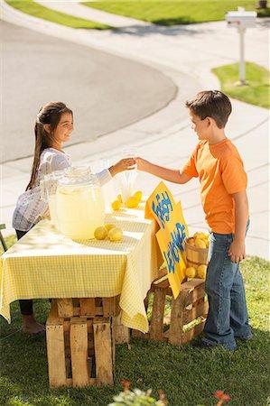 Boy buying lemonade at lemonade stand Stock Photo - Premium Royalty-Free, Code: 6113-07648870