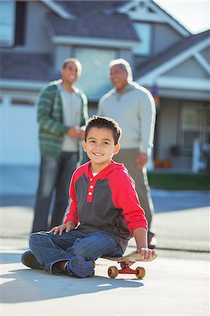 Portrait of smiling boy on skateboard in driveway Stock Photo - Premium Royalty-Free, Code: 6113-07648804
