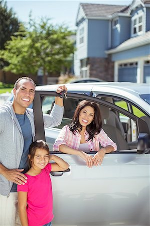 Portrait of smiling family at car in driveway Stock Photo - Premium Royalty-Free, Code: 6113-07648831