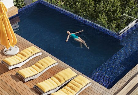 Woman floating in luxury swimming pool Stock Photo - Premium Royalty-Free, Code: 6113-07648932