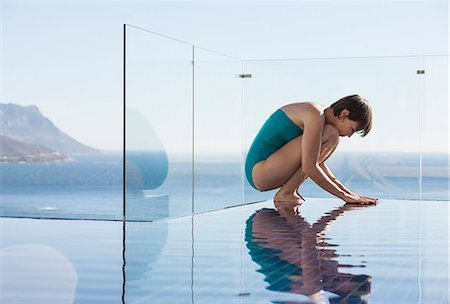 Woman crouching over infinity pool with ocean view Stock Photo - Premium Royalty-Free, Code: 6113-07648936