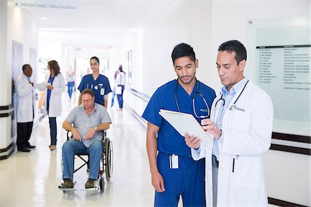 simsearch:6113-07146726,k - Doctor and nurse reading medical chart in hospital hallway Stock Photo - Premium Royalty-Free, Code: 6113-07761943