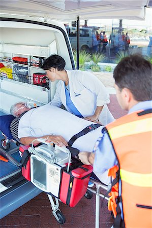 Doctor examining patient on ambulance stretcher Stock Photo - Premium Royalty-Free, Code: 6113-07761970