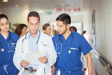 simsearch:6113-07146726,k - Doctor and nurses reading medical chart in hospital hallway Stock Photo - Premium Royalty-Free, Code: 6113-07761996