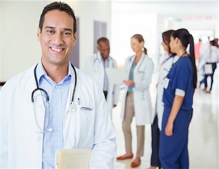 Doctor smiling in hospital hallway Stock Photo - Premium Royalty-Free, Code: 6113-07762072